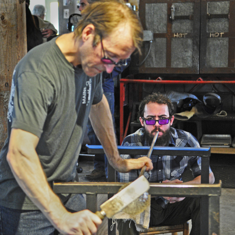 Charlie Jenkins, left, shapes a glass piece while Carel Shonerd blows on the metal tube to inflate it on Saturday at Tandem Glass in Dresden. Jenkins said that a lot of the time glass blowing is a group effort.