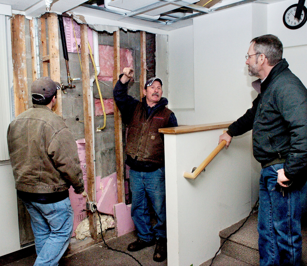Waterville City Engineer Greg Brown, right, confers on Thursday with Houle's Plumbing Heating & Air Conditioning employees Evan Thurlow, left, and Frank Lizotte near an opened wall at the Waterville Public Library, where cold air seeped into the library last weekend and froze a water pipe, causing it to burst and inflict serious damage on books and equipment.