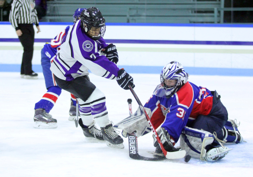 Waterville's Zach Menoudarakos tries to put the puck past Messalonskee  goalie Amber Kochaver during second-period action Thursday at Colby College in Waterville.