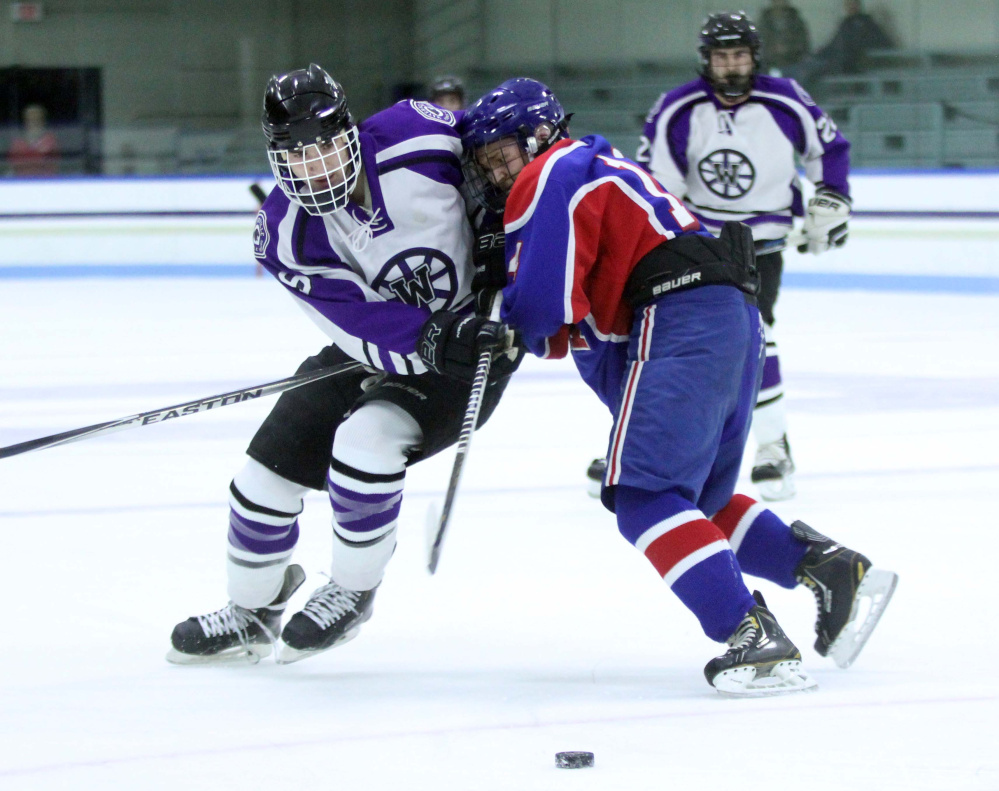 Waterville's Dalton Henderson, left, battles for the puck with Messalonskee's Dylan Cunningham during first-period action Thursday at Colby College in Waterville.
