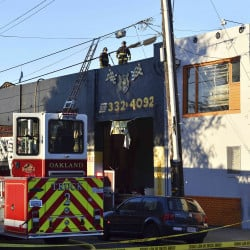 Firefighters assess the scene of the deadly warehouse fire in Oakland, Calif., on Saturday.