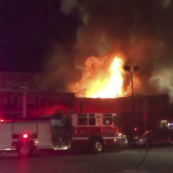 This photo taken from video provided by @Oaklandfirelive shows the scene of a fire in Oakland early Saturday.