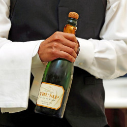 """A waiter opens a bottle of Trump champagne for the first guests to arrive at the Trump International Hotel on its """"soft opening"""" day in Washington on Sept. 12, 2016. Reuters/Kevin Lamarque"""