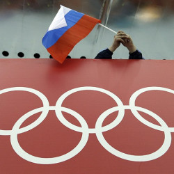 FILE - In this Feb. 18, 2014 file photo, a Russian skating fan holds the country's national flag over the Olympic rings before the start of the men's 10,000-meter speedskating race at Adler Arena Skating Center during the 2014 Winter Olympics in Sochi, Russia. The Olympic world is bracing for more evidence of systematic Russian doping. World Anti-Doping Agency investigator Richard McLaren is releasing his latest report on Friday Dec. 9, 2016 into allegations of state-sponsored cheating and cover-ups in Russia. (AP Photo/David J. Phillip, file)