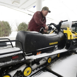 Steve Waugh of Mexico fuels his snowmobile at Loony Bin Variety on Main Street in Rangeley. Waugh is among those who feel a new trail to the lodge at the Saddleback ski area would help local businesses.