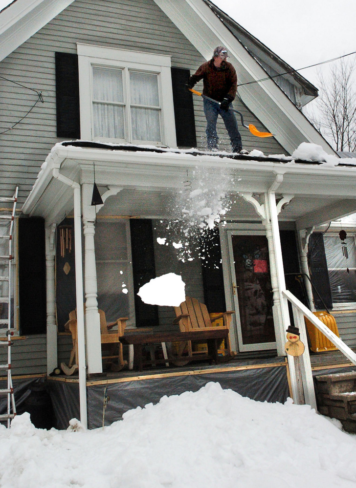 David Austin shovels snow from the roof of a friend's home Tuesday in Fairfield.