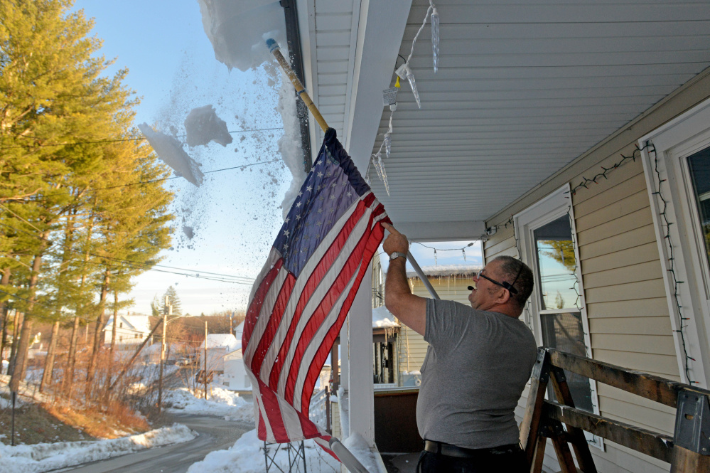 Richard Perkins clears his new porch roof from hanging snow and ice Thursday at his residence on Redington Street in Waterville.