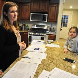 Stephanie Garofalo and her daughter Lydia, 6, stand around a kitchen island covered with papers about the Manchester Elementary School mold situation during an interview Tuesday at their Manchester home.