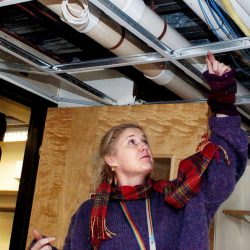 Waterville Public Library Director Sarah Sugden points to a water pipe below a drop ceiling on Dec. 19 that broke and flooded the library building and books. The library plans to close Jan. 25-31 to complete reconstruction from sustained water damage.