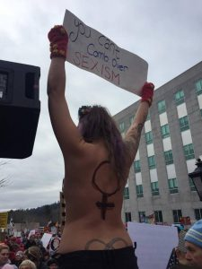 When Capitol Police tried to get this topless woman to step down from a pillar on Saturday at the Women's March on Maine rally in Augusta, the officer was bitten on the hand by another woman, police said.