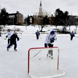 With the steeple on Miller Library at Colby College in the backdrop, members of the Colby men's hockey team skate during an outdoor scrimmage Monday at Johnson Pond.