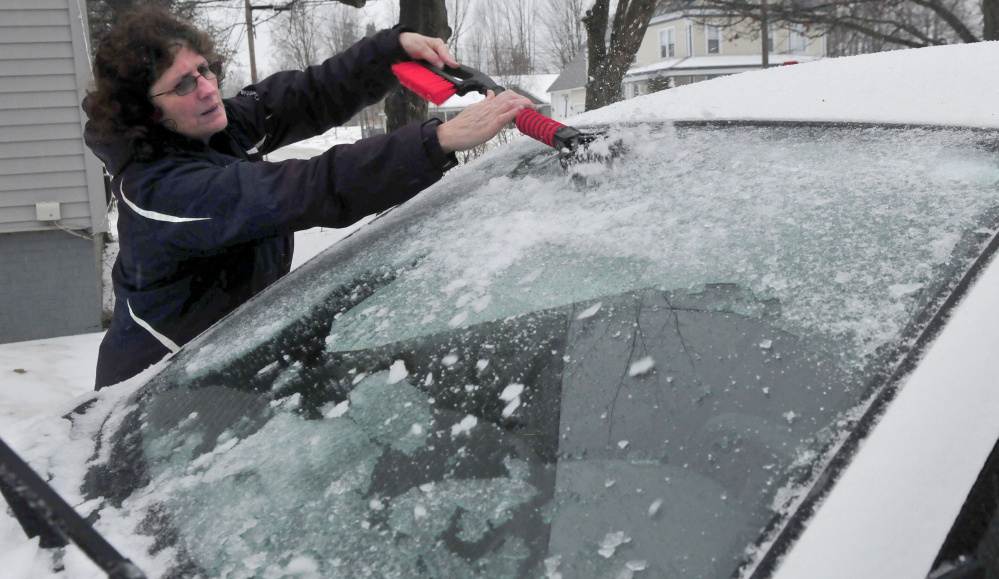 """Linda Hebert chips away at the ice that completely covered her car at her home in Fairfield during the storm on Tuesday. """"You have to be ready for anything in winter in Maine,"""" Hebert said."""