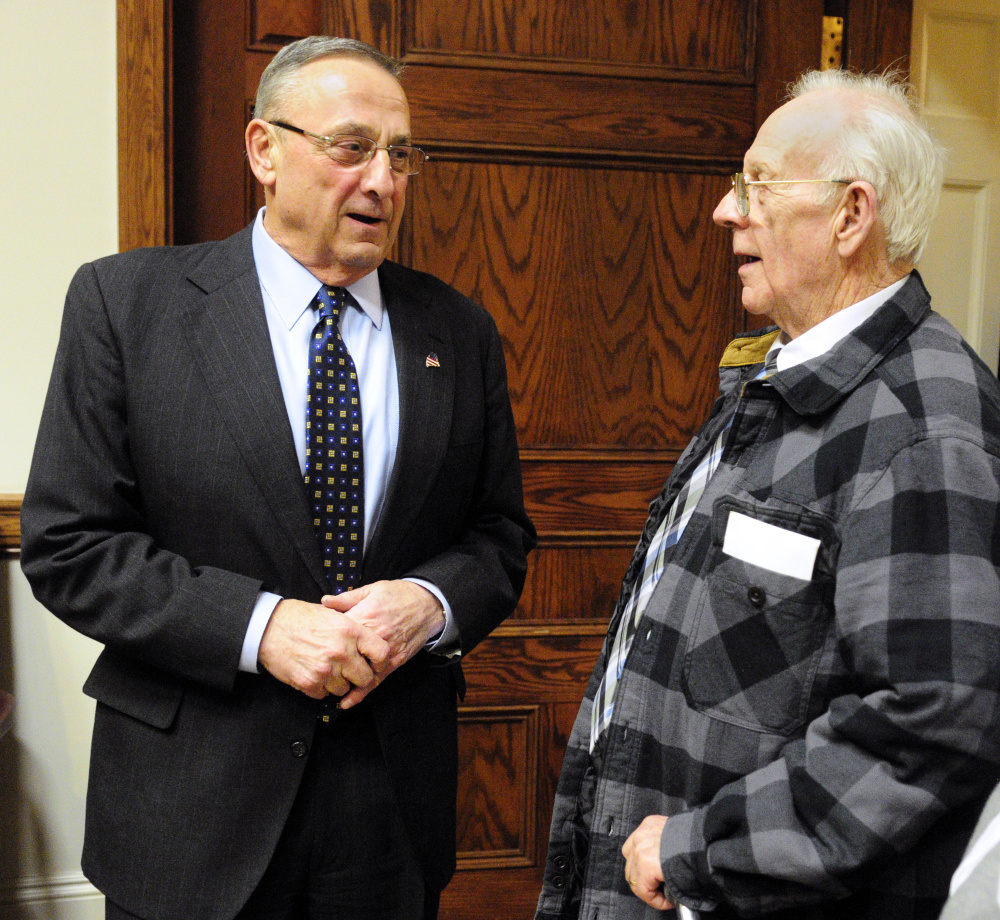 Gov. Paul LePage, left, chats with Richard Sukeforth at a Cabinet Room reception before the State of State address on Tuesday in the Maine State House in Augusta. Sukeforth and his wife lost their home when the town of Albion foreclosed and auctioned it off due to unpaid taxes. LePage mentioned wanting to change laws around that problem, citing the Sukeforths, during his speech.
