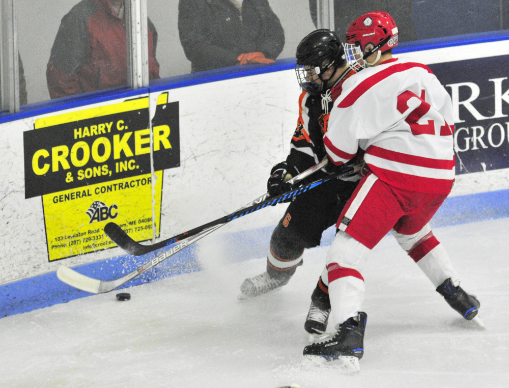Gardiner's Joe Clark, left, and Cony/Monmouth/Hall-Dale's Thomas Arps battle for a puck during a game Friday at the Camden National Bank Ice Vault in Hallowell.