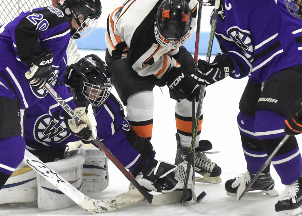 Waterville goalie Nathan Pinnate makes a save on a shot from Winslow forward Tommy Tibbetts (8) as Waterville defensemen Anthony Pinnette, left, and Matt Jolicoeur close in during a Class B North game Feb. 1 at Colby College.