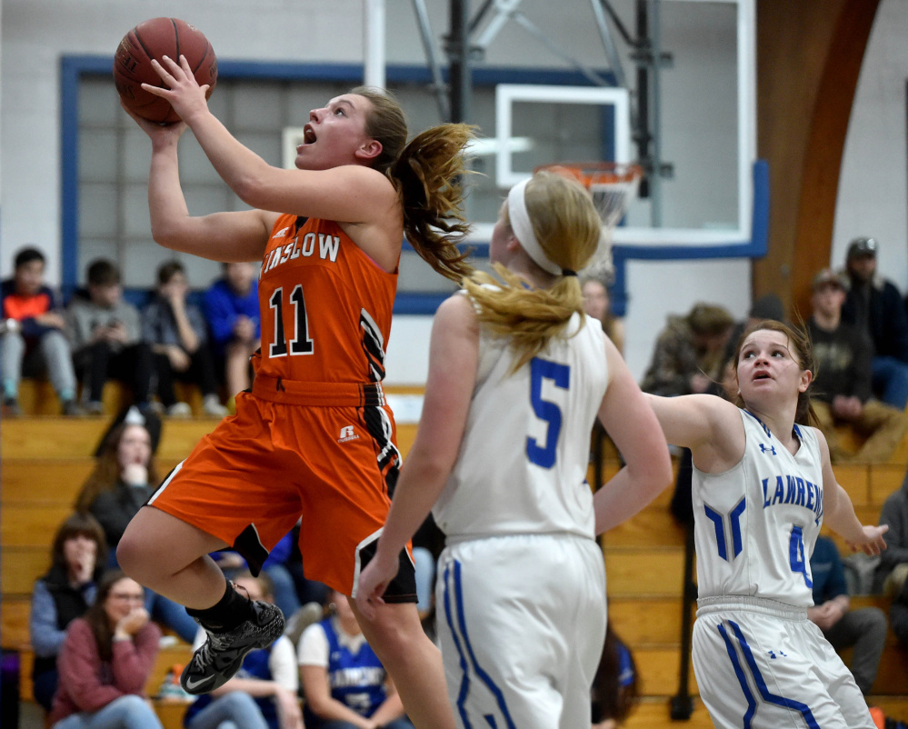 Winslow senior forward captain Heather Kervin (11) drives to the basket in front of Lawrence defender Brooklyn Lambert during the first quarter of a Kennebec Valley Athletic Conference game in Fairfield.