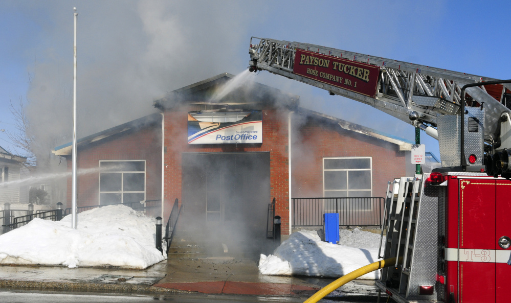 Firefighters work on scene on Tuesday at the post office in Winthrop, where firefighters from nine towns responded to help fight the blaze.