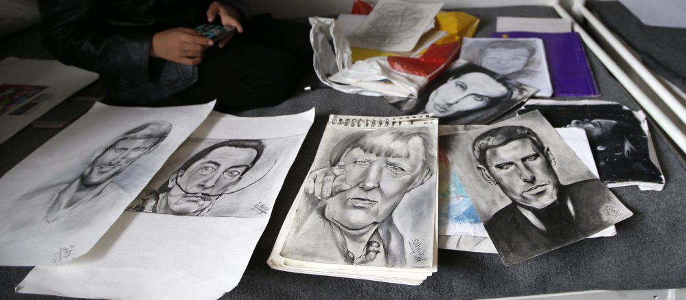 Farhad Nouri displays his portraits of Serbian tennis player Novak Djokovic, left, Spanish surrealist painter Salvador Dali, second from left, and German Chancellor Angela Merkel, third from left, in his family's room at a refugee camp near Belgrade, Serbia, on Monday.