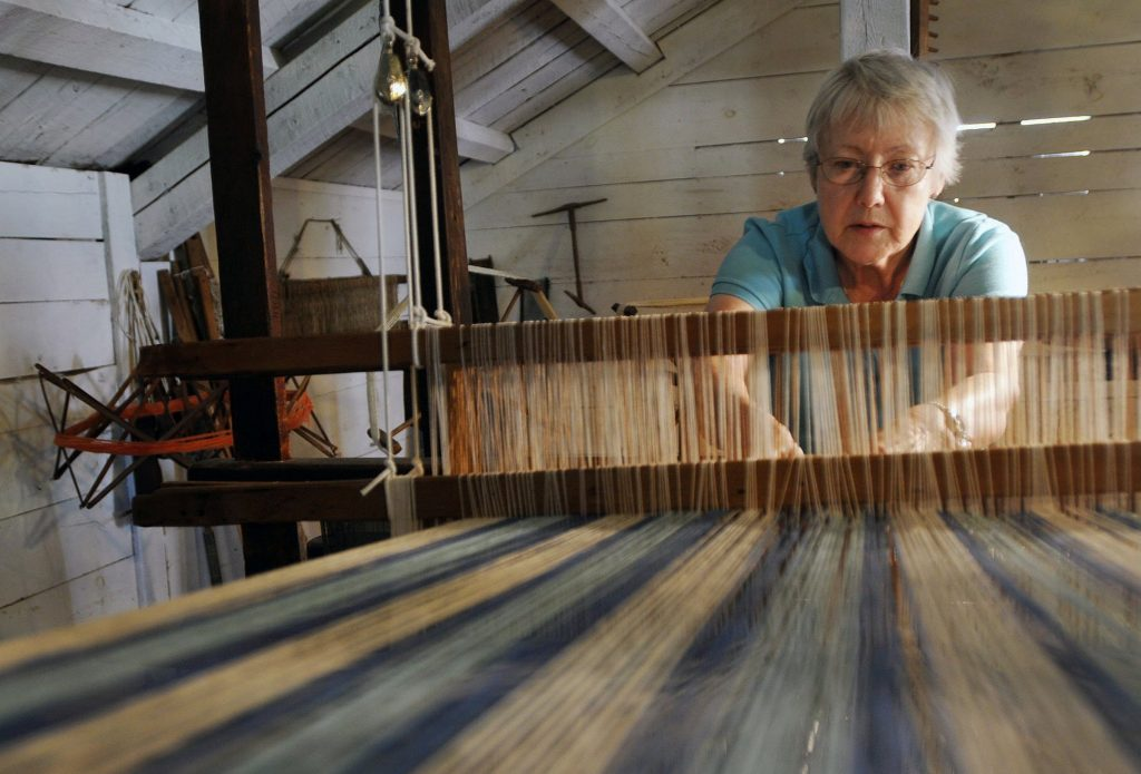 Paula Taggart of Parsonsfield, a volunteer with the 19th Century Willowbrook Village in Newfield, weaves with a barn loom in July 2011.