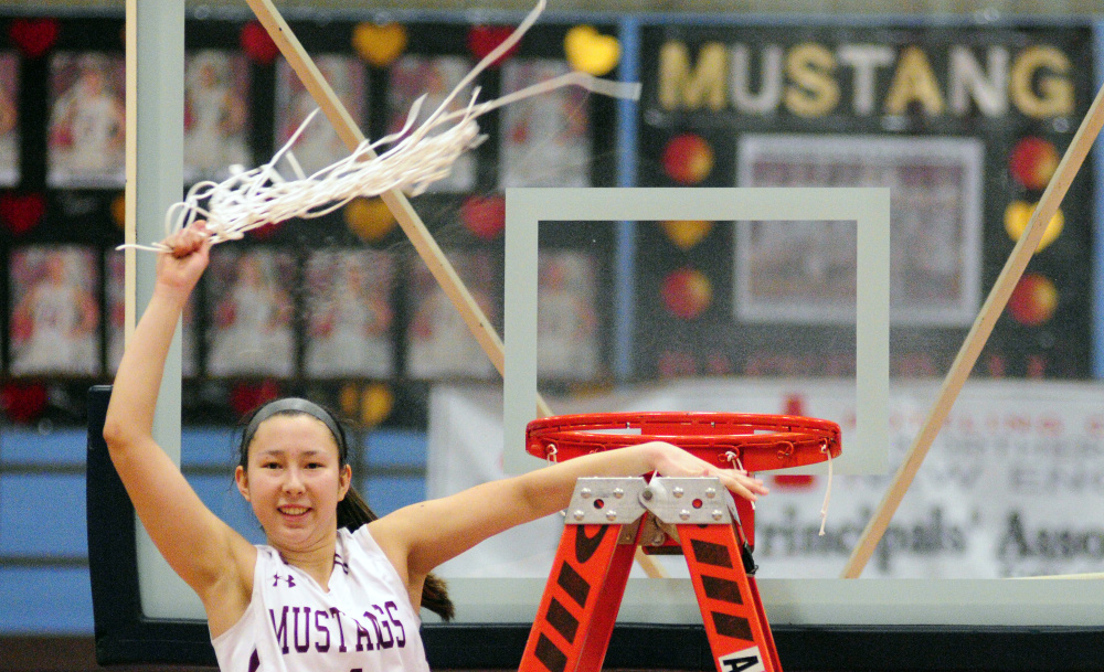 Monmouth's Tia Day swings a net in celebration after the Mustangs won the Class C South championship Saturday at the Augusta Civic Center. It was Monmouth's first regional title in Class C.