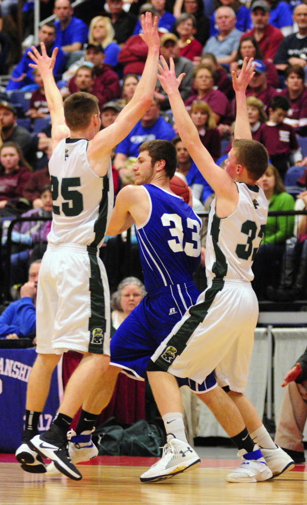 Madison's Mitchell Jarvais (33) gets double teamed by Winthrop defenders Garrett Tsouprake, left, and Nate LeBlanc in the Class C South championship game on Saturday at the Augusta Civic Center.