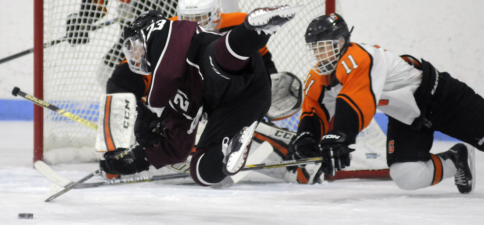 Gardiner's Sloan Berthiaume, right, stops Gorham's Adam Peterson during a Class B South quarterfinal game last season at the Camden National Bank Ice Vault in Hallowell.