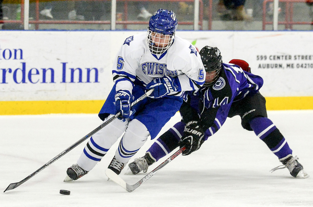 Waterville's Michael Bolduc, right, fights for control of the puck with Lewiston's Sam Story in the first period of their game on Feb. 28 at the Androscoggin Bank Colisee in Lewiston.