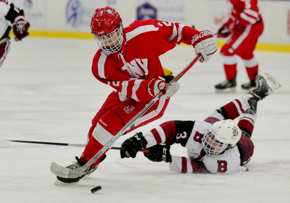 Bangor's Charlie Budd takes a swipe at the feet of Cony's Avery Pomerleau in a fight over the puck in the second period of the Class A North semifinals Saturday in Lewiston.