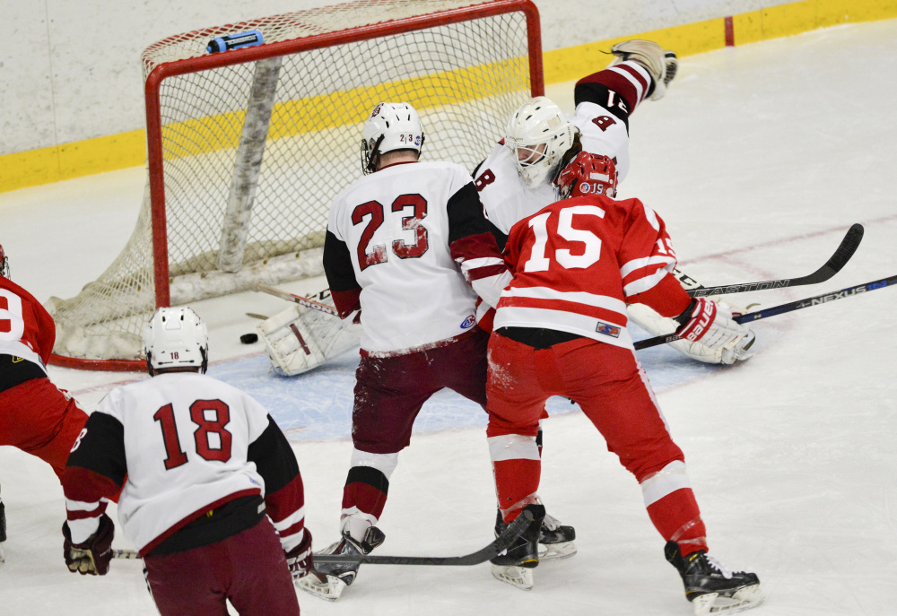 Cony's Cam Wilson, left, scores a goal past Bangor goalie Zach Alden in the first period of the Class A North semifinal Saturday in Lewiston. Bangor went on to win 2-1.