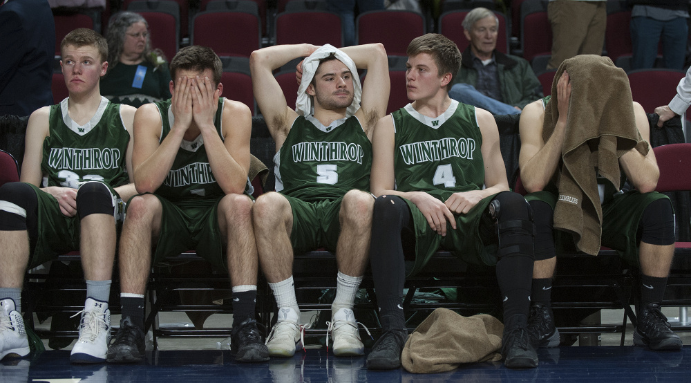Members of the Winthrop boys basketball team react after George Stevens Academy won the Class C sate title Saturday at the Cross Insurance Center in Bangor.