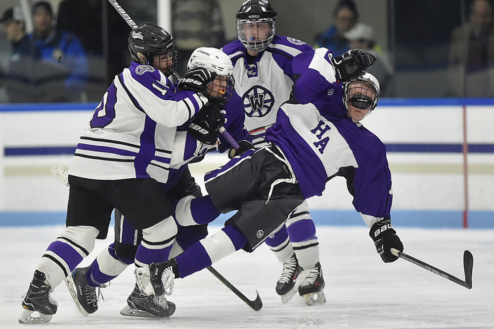 Waterville defenseman Matt Jolicoeur, left, checks Hampden's Mark Thibodeau, center, and Cooper Leland during a Class B North semifinal Saturday night at Alfond Rink in Waterville.