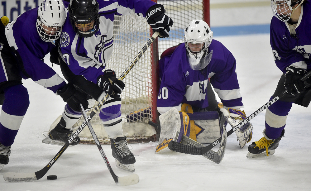 Waterville forward Zack Menoudarakos (7) battles for the puck with Hampden defenseman Jacob Weston as Hampden goalie Cole Benner looks on during a Class B North quarterfinal game last Saturday in Waterville.