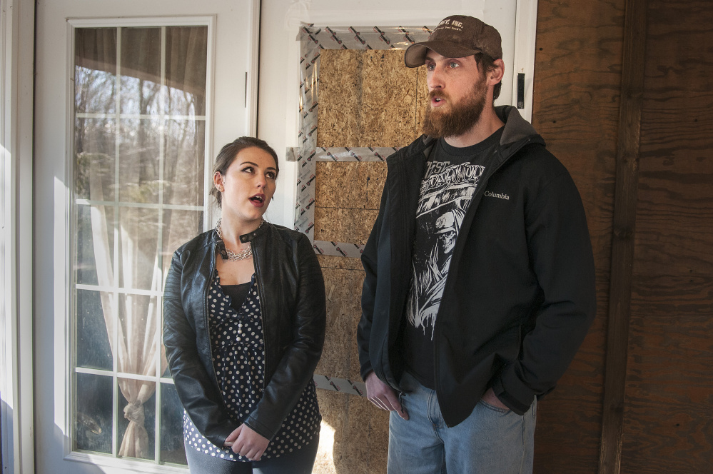 Standing in front of the boarded-over broken window of their front door, Lindsey Levasseur, left, and Trevor Whitney tell the story of an early morning home invasion Wednesday at their apartment in Richmond.