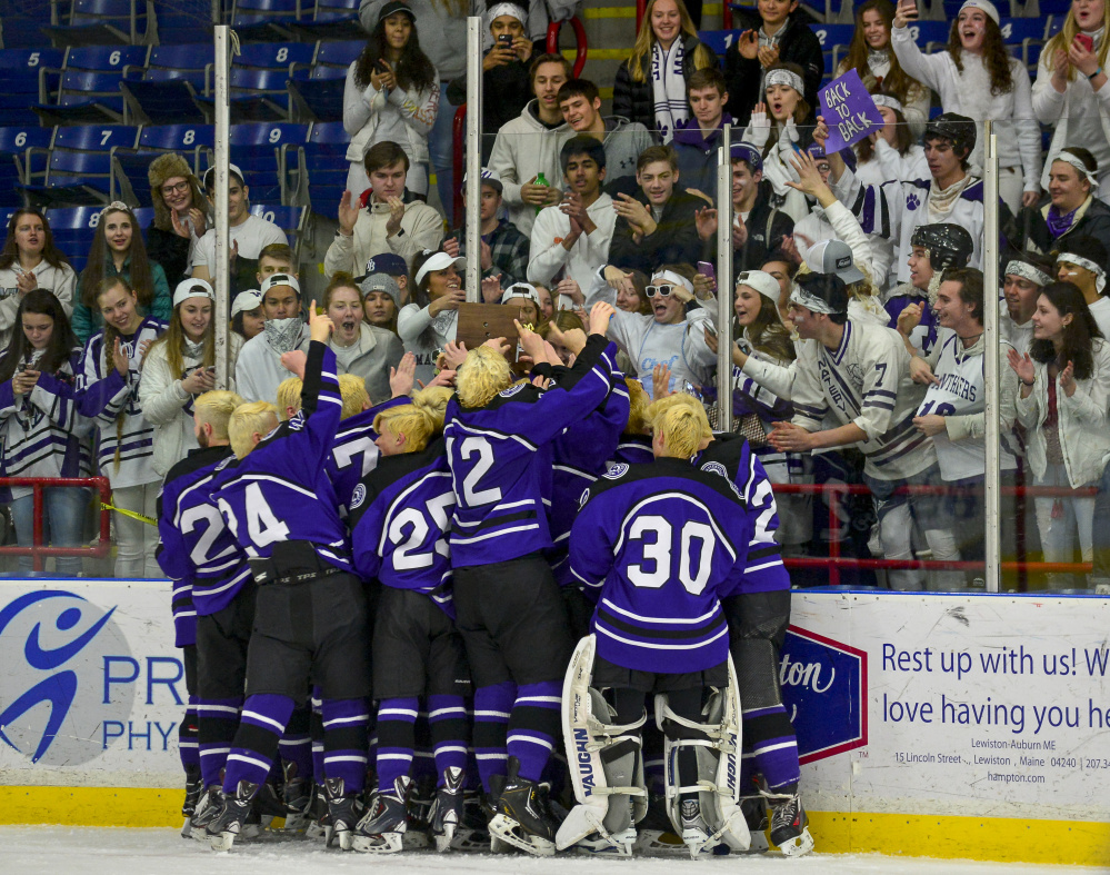Members of the Waterville hockey team celebrate in front of student supporters after the Panthers upended York 7-4 in the Class B state championship game Saturday in Lewiston.