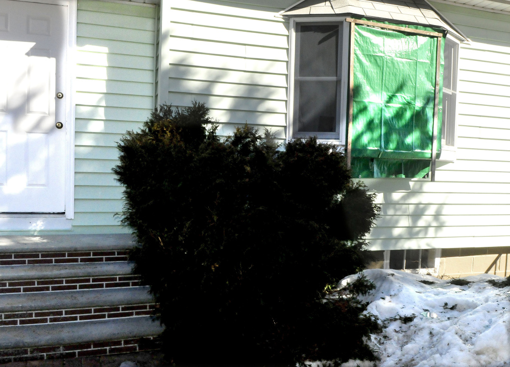 A tarp covers a broken front window at the Audrey Hewett residence at 47 Lyons Road in Sidney on Monday. Police allege a male intruder, Dreaquan Foster, was confronted Sunday evening by Hewett's son Eric, who was injured after being struck by a blunt object. In the scuffle Eric Hewett shot Foster in the chest.
