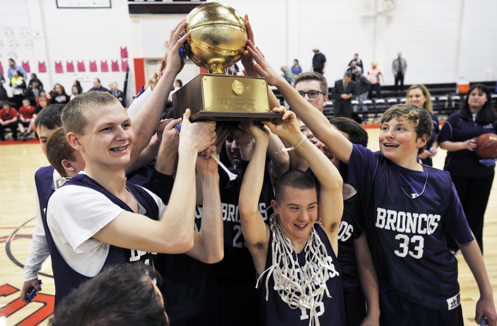 Hampden Academy unified basketball players celebrate with a Gold Ball after winning the state championship last season.