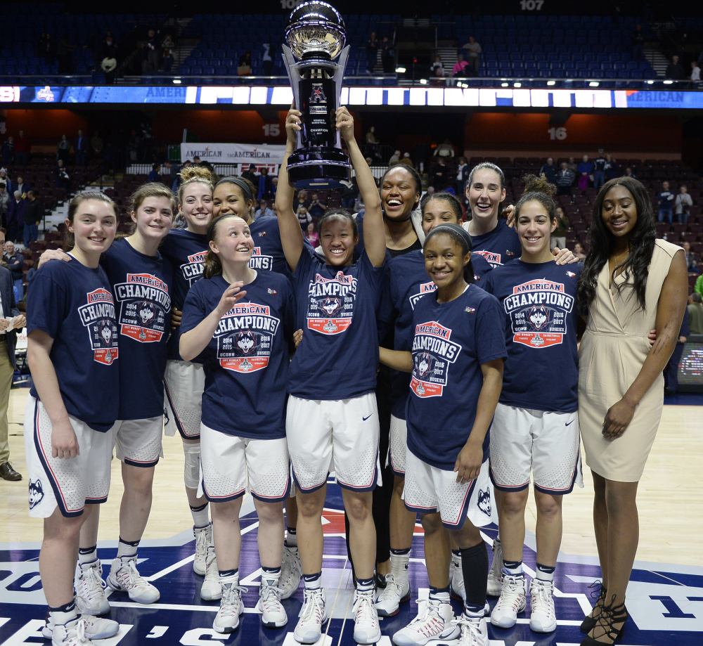 The Connecticut women's basketball team pose with the American Athletic Conference championship trophy after defeating South Florida on March 6 in Uncasville, Connecticut.