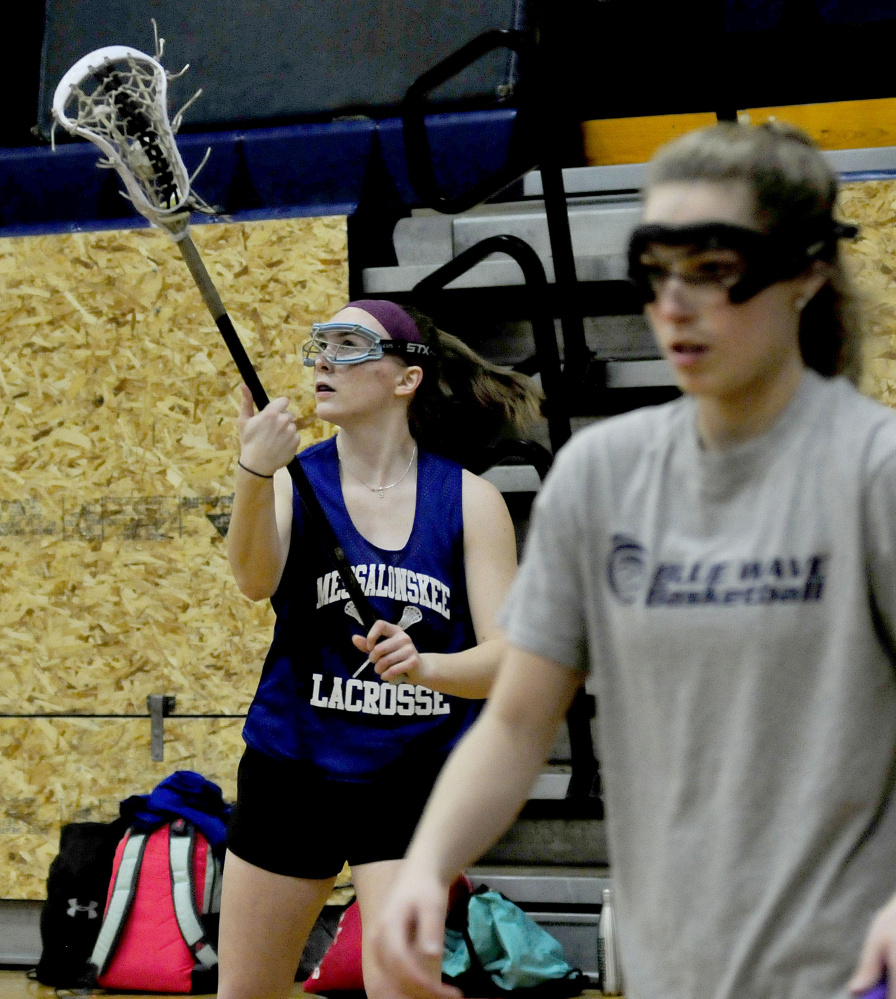 Messalonskee girls lacrosse player Autumn Littlefield, left, catches ball as teammate Sophie Holmes participates in a drill during practice Wednesday at the high school.