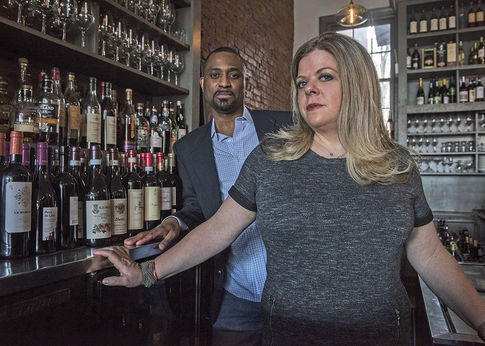 Khalid Pitts, left, and Diane Gross, co-owners of Cork, a Washington, D.C., wine bar, are suing President Donald Trump, alleging his continued ownership of a downtown hotel constitutes unfair competition that damages their business.