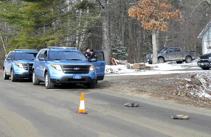 Two Maine State Police troopers consult outside a residence on Winnecook Road in Burnham while investigating the death of Joyce Wood on Sunday. A pair of boots lie in the road in foreground.