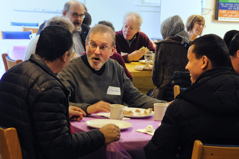 Adnan Kadhim, left, the Rev. Frank Morin, and Hassan Nasar chat over lunch on Saturday at Prince of Peach Lutheran Church in Augusta during a meeting to discuss creating a community center to welcome new residents.