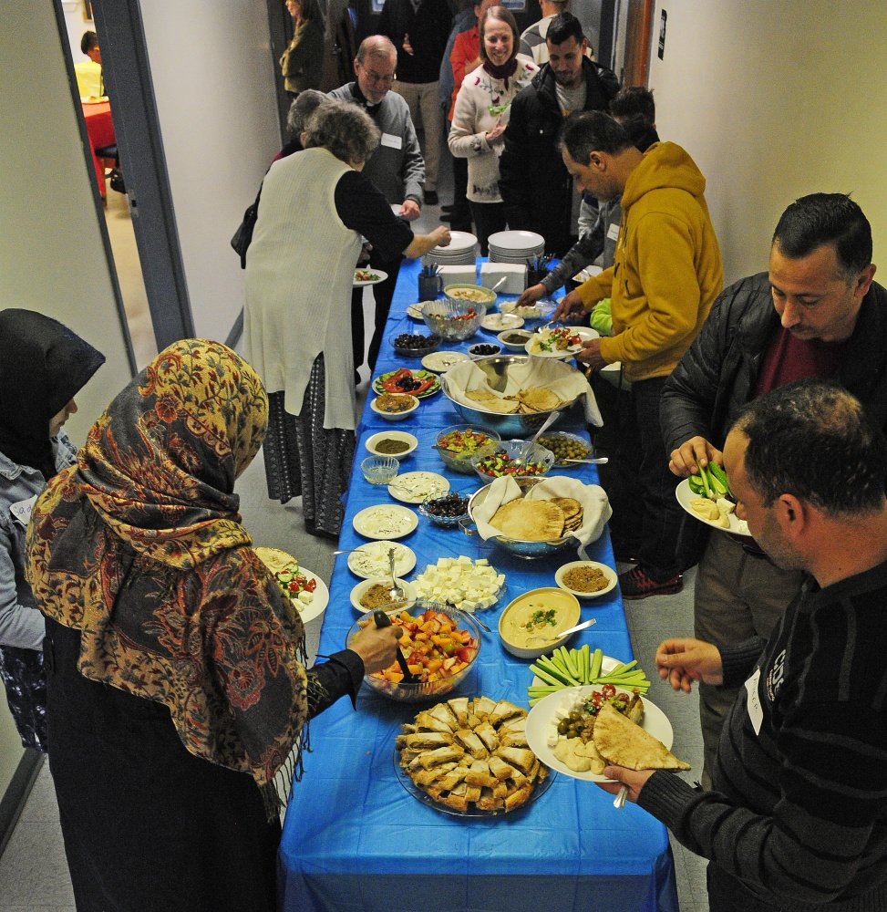 People serve themselves lunch from the buffet table on Saturday during a meeting at Prince of Peach Lutheran Church in Augusta to discuss creating a community center to welcome new residents.