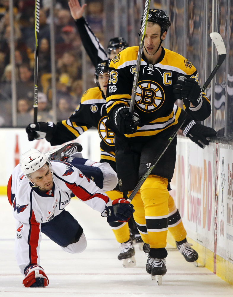 Washington Capitals forward Matt Niskanen (2) is knocked to the ice by Boston defenseman Zdeno Chara during the second period of a game Saturday in Boston.