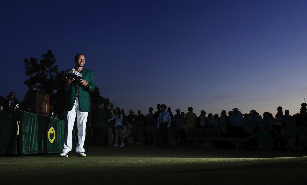 Sergio Garcia holds up his winning trophy at the green jacket ceremony after the Masters on Sunday.