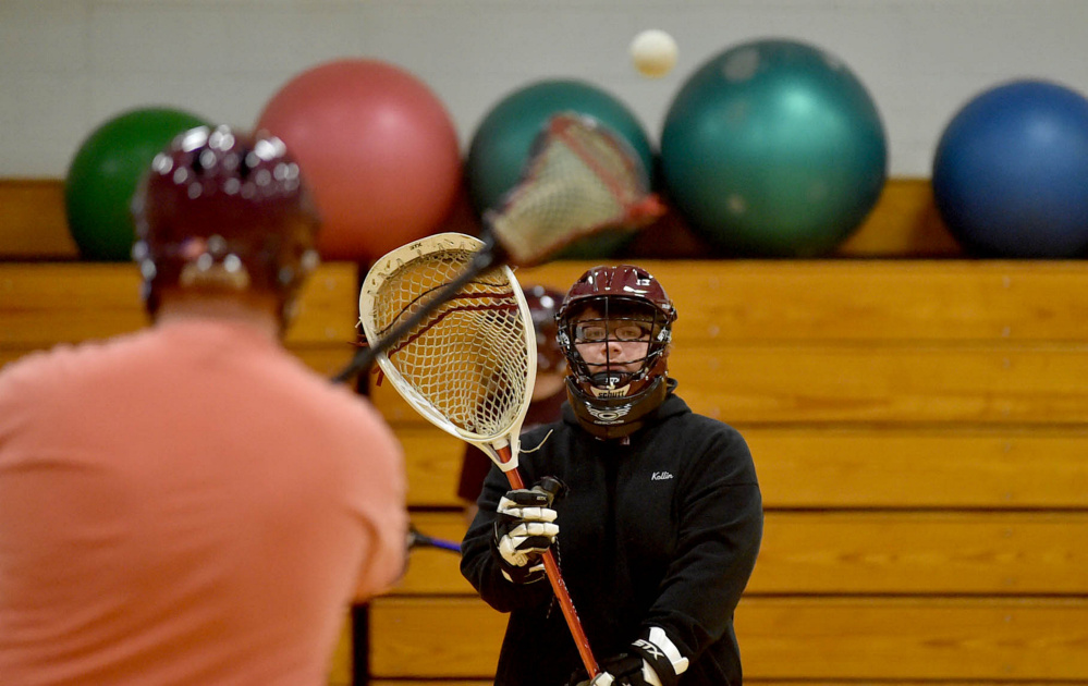 Senior Kollin Cobb, facing, plays pass with teammate Sam Goodsoe, left, during the first practice for the combined Nokomis and Maine Central Institute lacrosse team Tuesday at Maine Central Institute in Pittsfield.