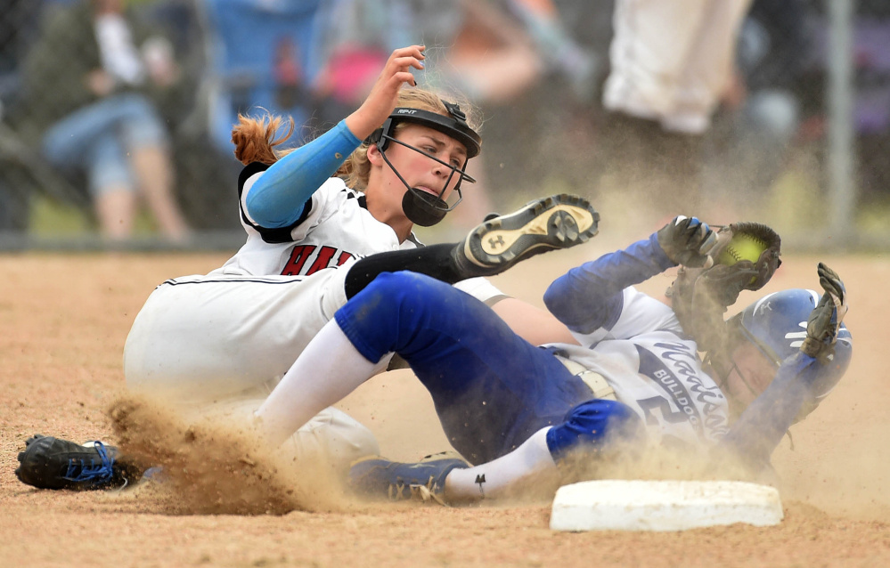 Heads up: Hall-Dale shortstop Alyssa Bonenfant, left, tags out Madison runner Ashley Emery at second base during a Class C South semifinal game last season in Madison.