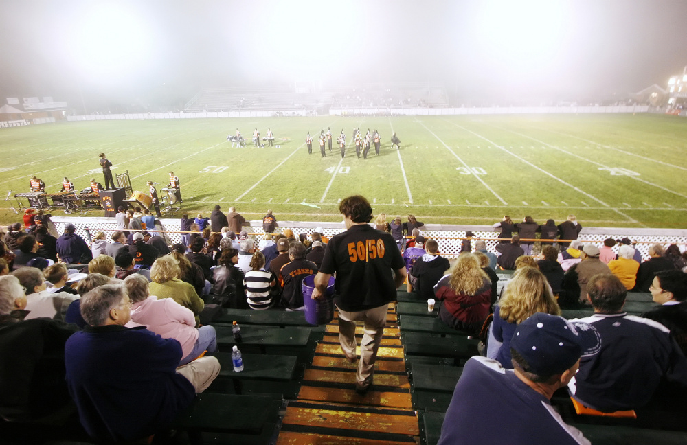 In this 2007 file photo, Don Houde sells raffle tickets in the bleachers during halftime of a game at Waterhouse Field in Biddeford. It was announced last week that field will not host the annual Lobster Bowl Classic and will be closed for the upcoming football season after an independent study showed the bleachers were too dangerous to sit in.
