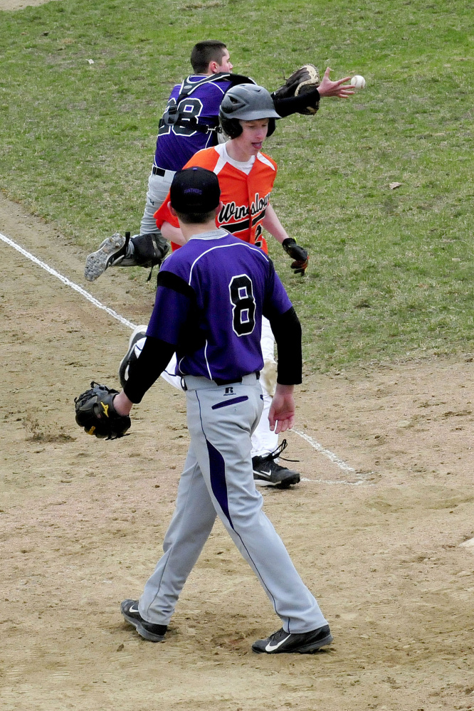 Waterville catcher Daniel Gaunce catches the ball as Winslow's Tom Tibbetts crosses home plate and Waterville pitcher Cody Pellerin (8) backs up the play Wednesday in Waterville.