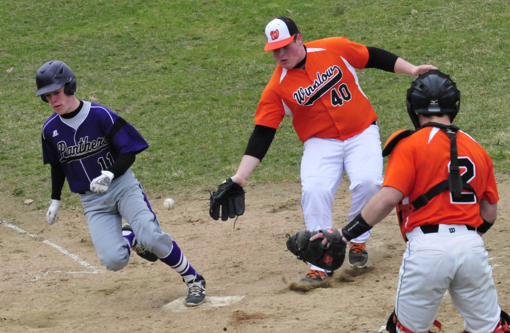 Winslow's Cam Winslow (40) reaches for the ball as Waterville's Jackson Aldrich scores during a game Wednesday in Waterville. Winslow catcher Patrick Hopkins backs up play.