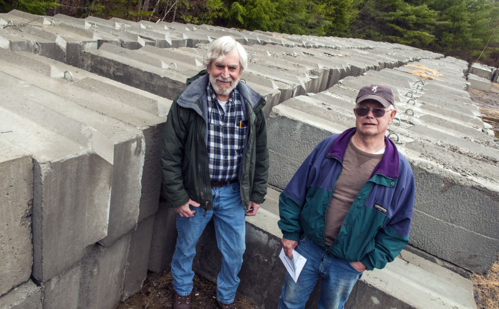 President Scott Farnum, left, and Treasurer Paul Okerholm pose for a portrait Thursday with hundreds of cement blocks that will form the new side walls at the West Gardiner Rod & Gun Club gun range behind the clubhouse.
